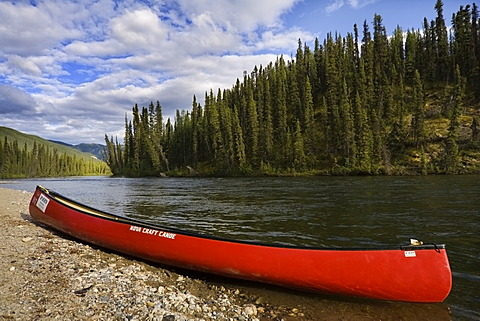 Red canoe on the shore of Big Salmon River, Yukon Territory, Canada, North America