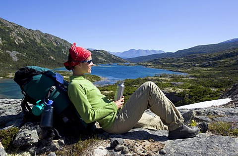 Young woman resting, hiker with backpack, water bottle, panorama, deep lake behind, historic Chilkoot Trail, Chilkoot Pass, alpine tundra, Yukon Territory, British Columbia, B. C., Canada