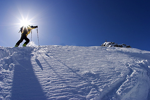 Ski touring person directly under the sun with ski sticks yellow jacket in a winter landscape wirh snow and blue sky at the Scheinbergspitze close to castle Linderhof in Germany