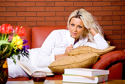 Young woman lying on a sofa in the living room, books