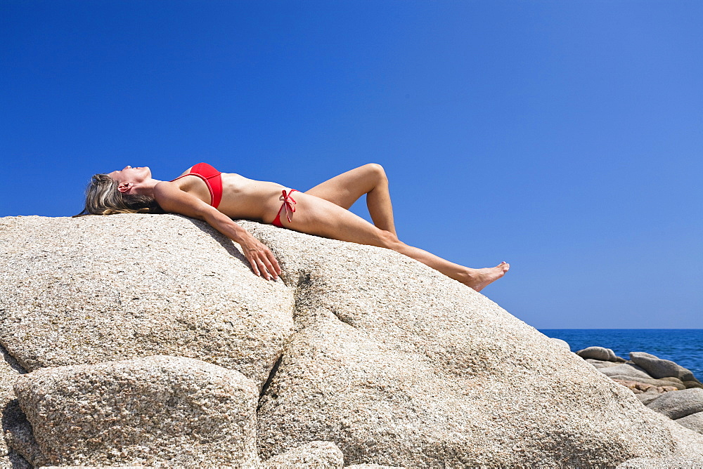 Woman sunbathing on the rocks of Palombaggia beach, south-east coast, Balagne region, Corsica, France, Europe