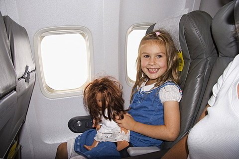 Little girl with doll in airplane
