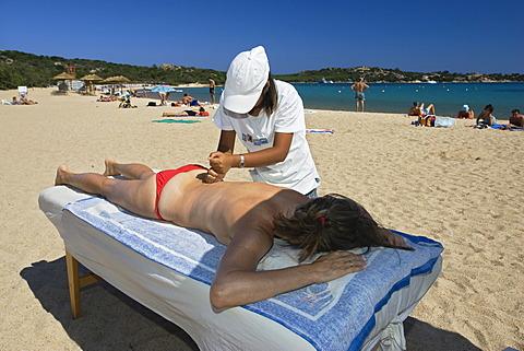 Chinese girl giving massage on the beach, Costa Smeralda, Sardinia