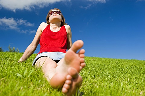 Young woman sitting barefoot in summer meadow relaxing