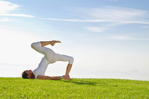 Young woman practising Hatha yoga, here a variation of halasana, supta konasana, variation of plough