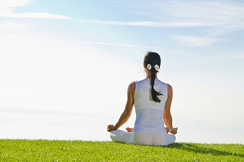 Young woman practising Hatha yoga, here the pose padmasana, lotus pose