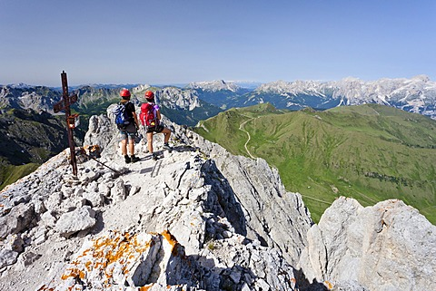 Climber on the summit of Colac on the Via Ferrata dei Finanzieri in Val di Fassa, Dolomites, behind the Rose Garden Group and the Latemar, Trentino Province, Italy, Europe