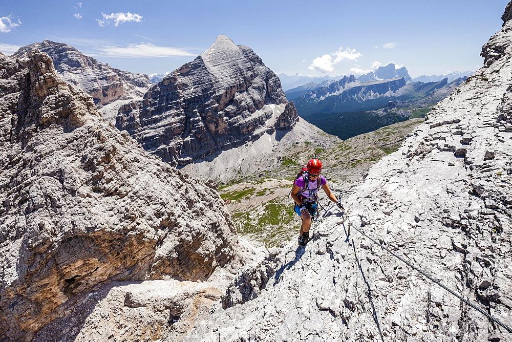 Mountaineer, Via Ferrata Tomaselli, southern Fanes peak, Tofana di Rozes, Tofana di Mezzo and Pelmo behind, Dolomites, Belluno, Alps, Italy, Europe