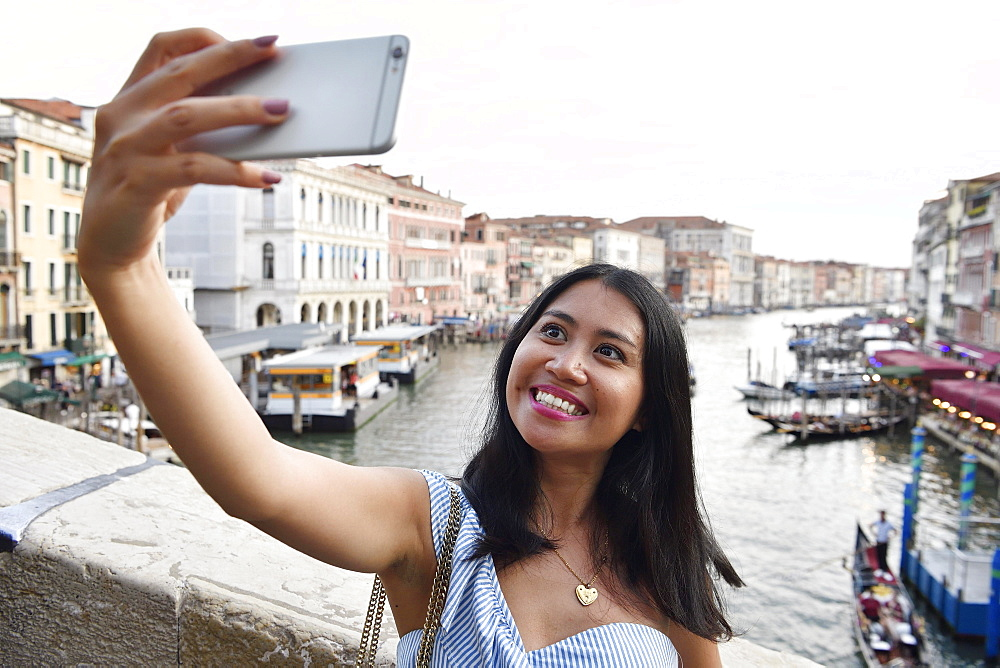 Woman taking a Selfie with mobile phone, Rialto bridge, Canale Grande, Venice, Venice, Venice, Italy, Europe