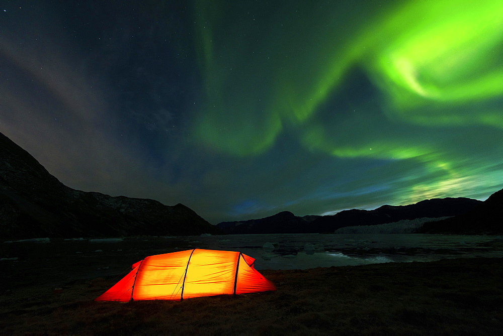 Northern lights, illuminated tent by the fjord, West Greenland, Greenland, North America