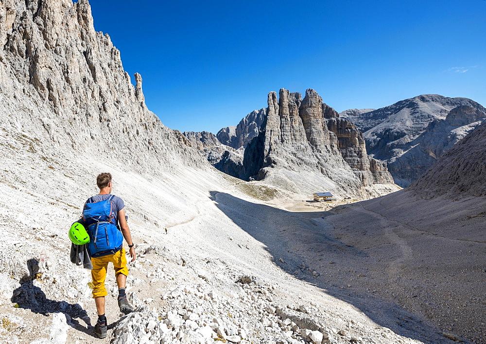 Hiker descending from the Santner via ferrata to the Gartl hut, Rifugio Re Alberto, at the back climbing cliffs, Vajolett towers, Rosengarten group, Dolomites, South Tyrol, Trentino-Alto Adige, Italy, Europe