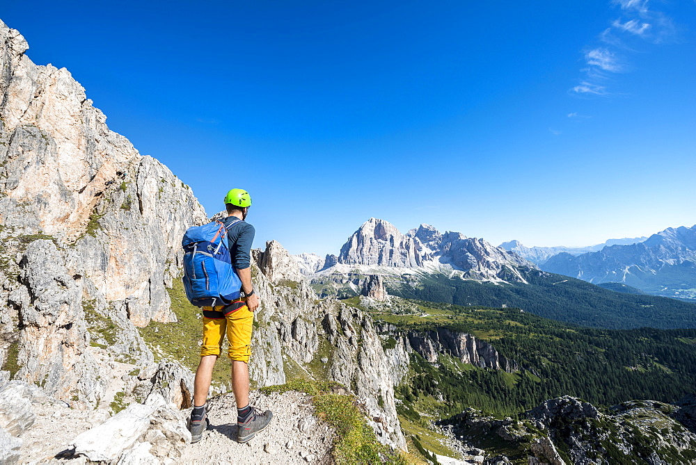 Hiker with climbing helmet on hiking trail to the Nuvolau, view of the mountain range Tofane, Dolomites, South Tyrol, Trentino-Alto Adige, Italy, Europe