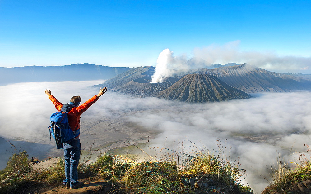 Young man with raised arms in front of volcanic landscape, view in Tengger Caldera, smoking volcano Gunung Bromo, in front Mt. Batok, in the back Mt. Kursi, Mt. Gunung Semeru, National Park Bromo-Tengger-Semeru, Java, Indonesia, Asia