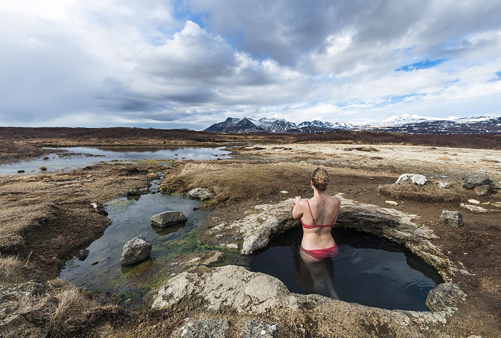 Young woman in hot spring looking towards mountains, Eyjar og Miklaholt, Western Region, Iceland, Europe