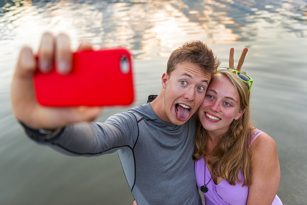 Young couple photographing themselves with mobile phone, selfie, Schliersee, Upper Bavaria, Bavaria, Germany, Europe