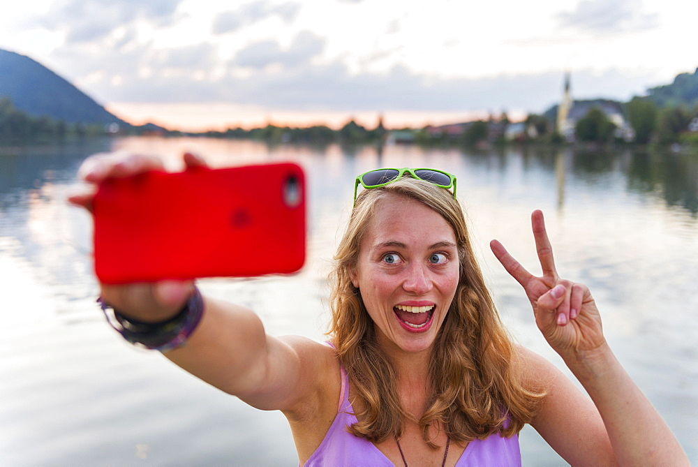 Young woman taking selfie, laughing and making peace sign, Schliersee, Upper Bavaria, Bavaria, Germany, Europe