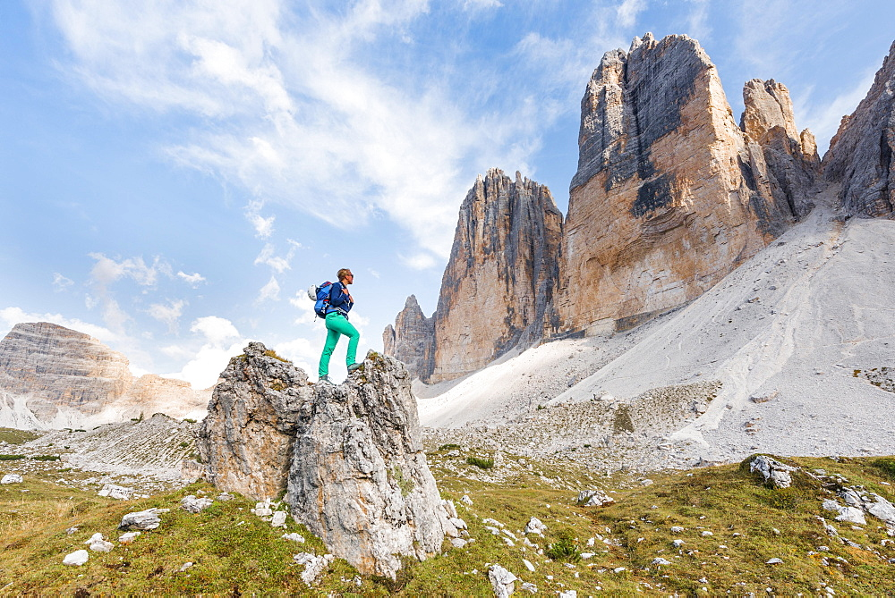 Hiker stands on rocks, north faces of the Three Peaks of Lavaredo, Sesto Dolomites, South Tyrol, Trentino-South Tyrol, Alto-Adige, Italy, Europe