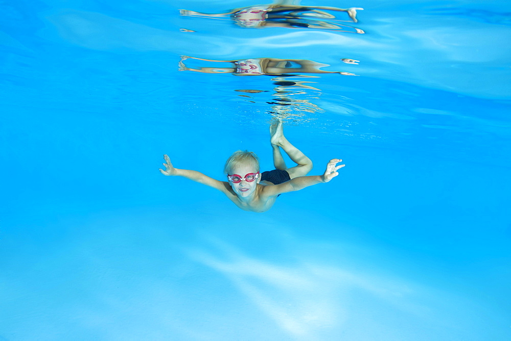 Little boy with swimming goggles, learning to swim underwater in the pool, Ukraine, Europe