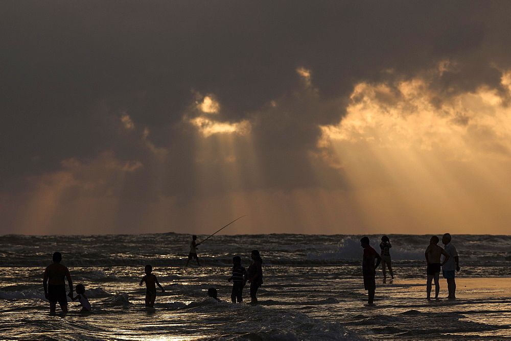 People in backlight on beach, rays of sunlight, dark clouds over sea, Beruwela, Western Province, Sri Lanka, Asia