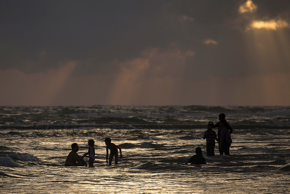 People in backlight in water, rays of sunlight, dark clouds over sea, Beruwela, Western Province, Sri Lanka, Asia
