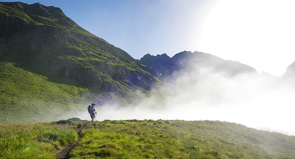 Hiker on the Schladminger Höhenweg with rising clouds of fog, Schladminger Tauern, Schladming, Steiermark, Austria, Europe