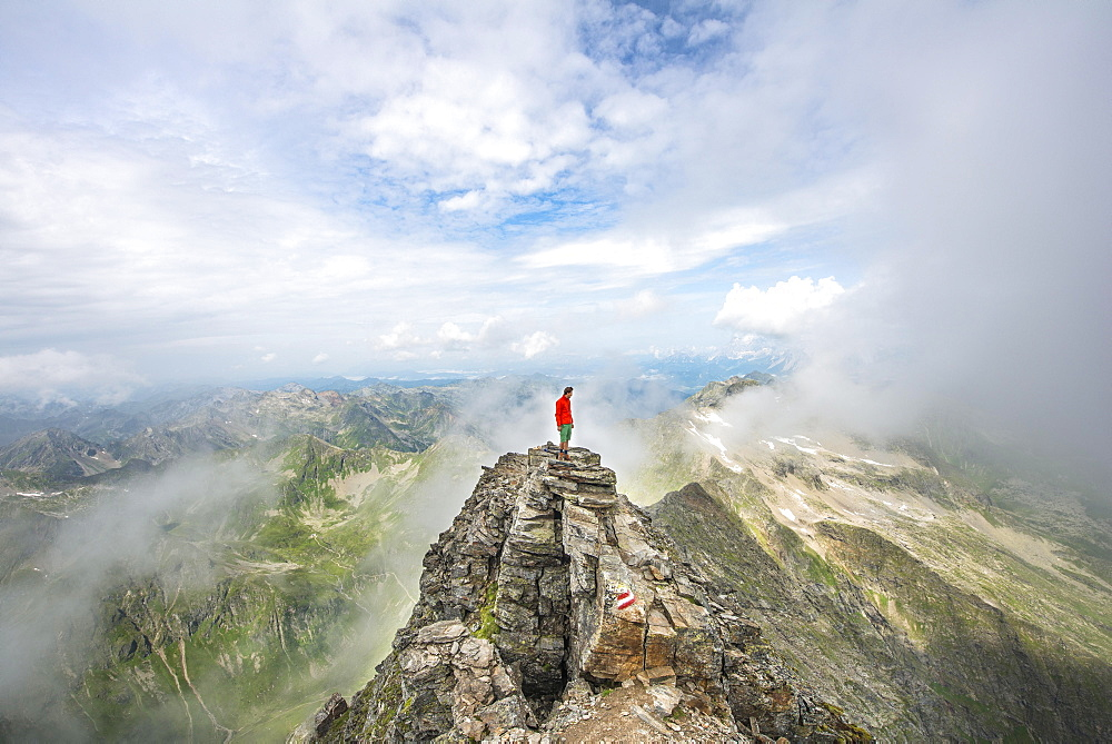 Hiker on the summit of the Hochgolling with rising fog, Schladminger Höhenweg, Schladminger Tauern, Schladming, Steiermark, Austria, Europe