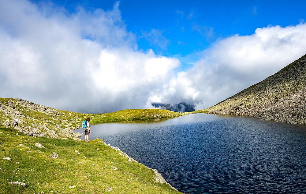 Hiker at Sattelsee lake at Greifenbergsattel, ascent to Greifenberg, Schladminger Höhenweg, Schladminger Tauern, Schladming, Styria, Austria, Europe