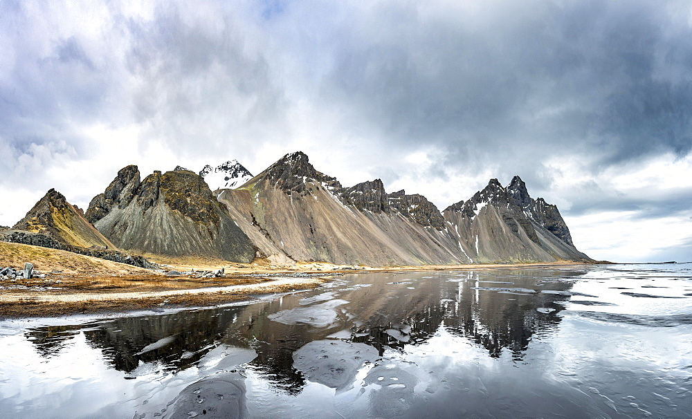 Water reflection, mountains Klifatindur, Eystrahorn and Kambhorn, Stokksnes headland, Klifatindur mountain range, Eastern Region, Iceland, Europe