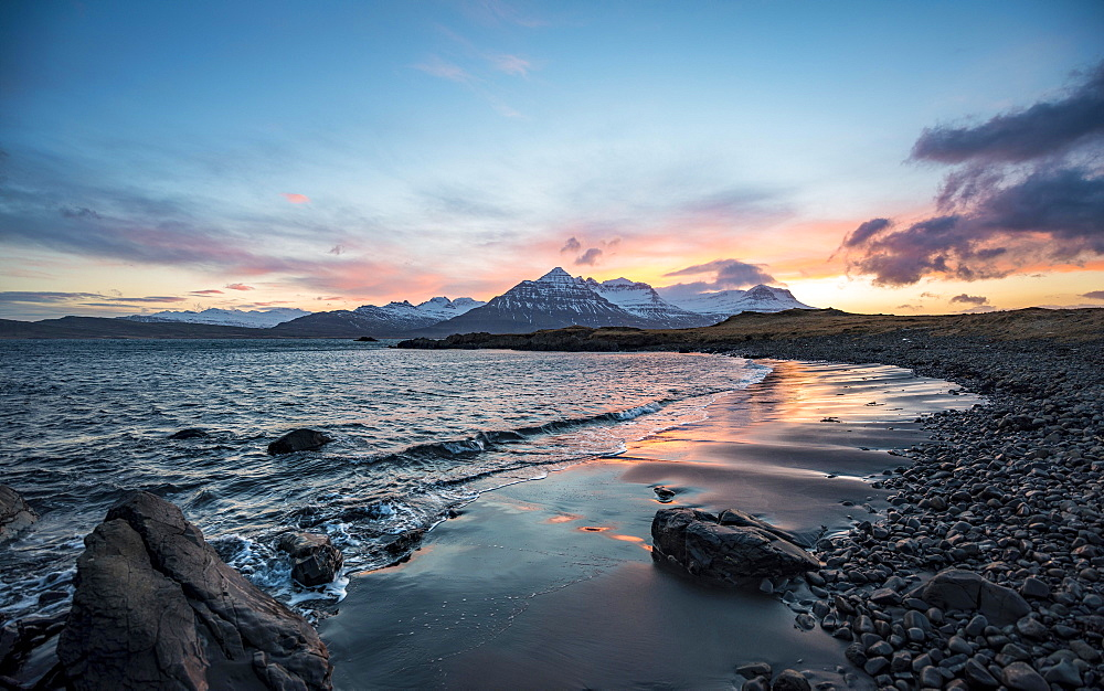 Sunset over snow covered mountains, small bay with black beach at the fjord Berufjorour, Austurland, East Iceland, Iceland, Europe