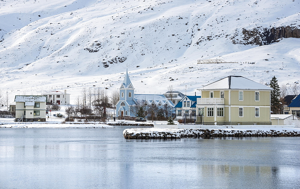 View of the blue church Seyoisfjaroarkirkja in the village Seyoisfjorour with snow, reflection in the lake Fjaroara, Austurland, East Iceland, Iceland, Europe