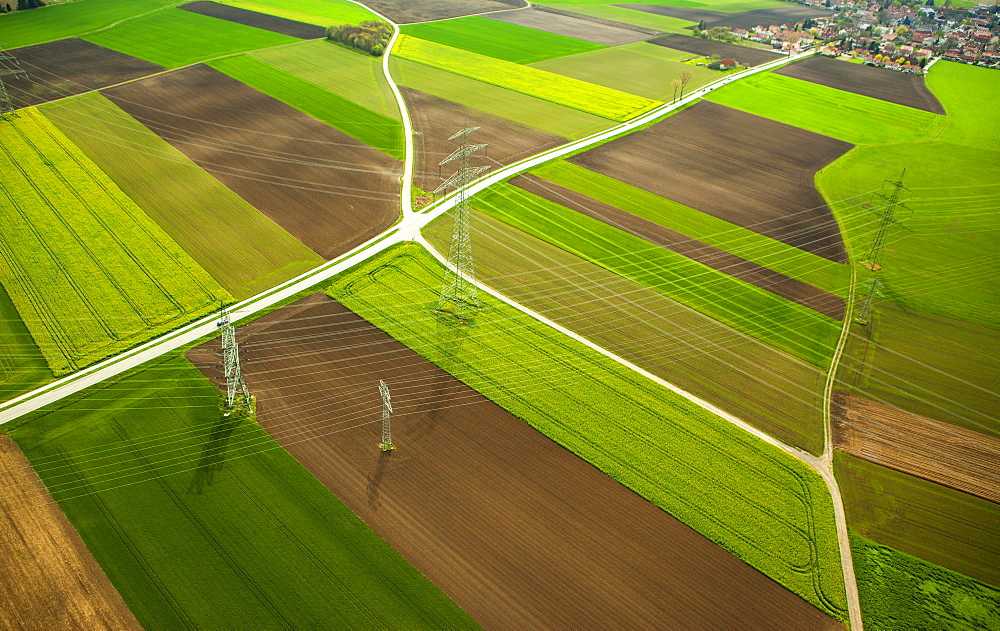 High-voltage transmission lines over farm fields in spring, aerial view, in Moosinning, Upper Bavaria, Bavaria, Germany, Europe