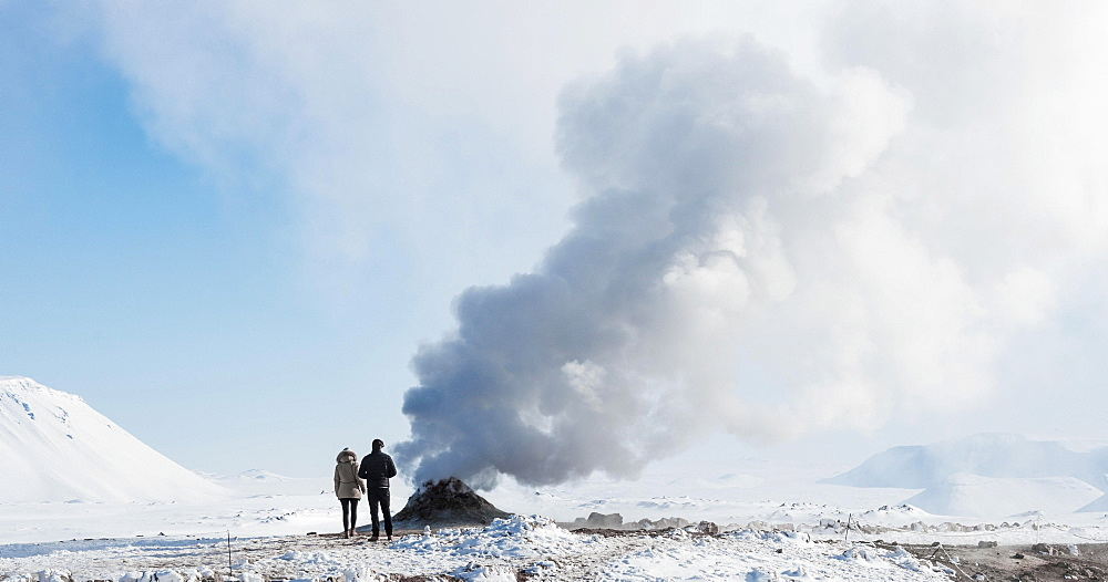Two tourists standing beside steaming fumarole, solfatara in Hverarond, also Hverir or Namaskard, geothermal area, North Iceland, Iceland, Europe