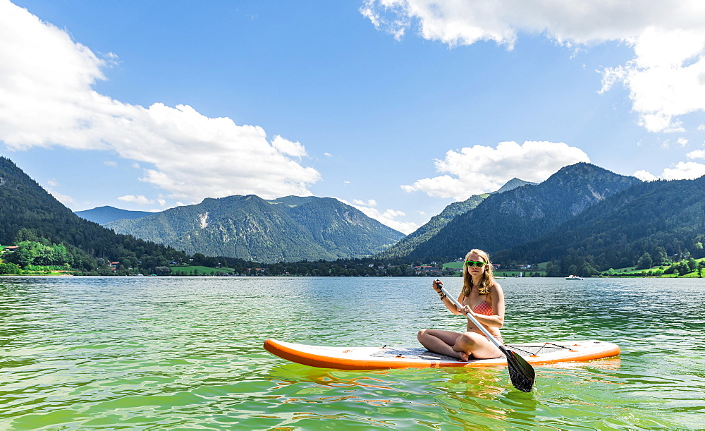 Young woman sitting on a Standup-Paddle Board or SUP, behind mountains, Schliersee, Upper Bavaria, Bavaria, Germany, Europe