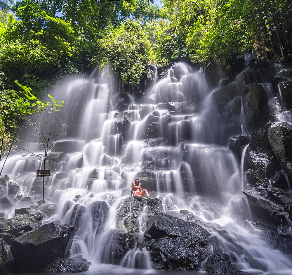 Woman sitting on rock, waterfall, Air Terjun Kanto Lampo, near Ubud, Bali, Indonesia, Asia