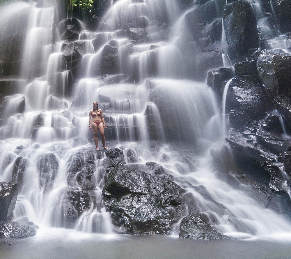 Woman standing in waterfall, Air Terjun Kanto Lampo, near Ubud, Bali, Indonesia, Asia