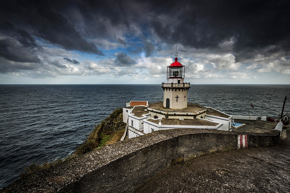 Lighthouse Farol da Ponta do Arnel at the sea, dark clouds, north-east, Sao Miguel, Azores, Portugal, Europe