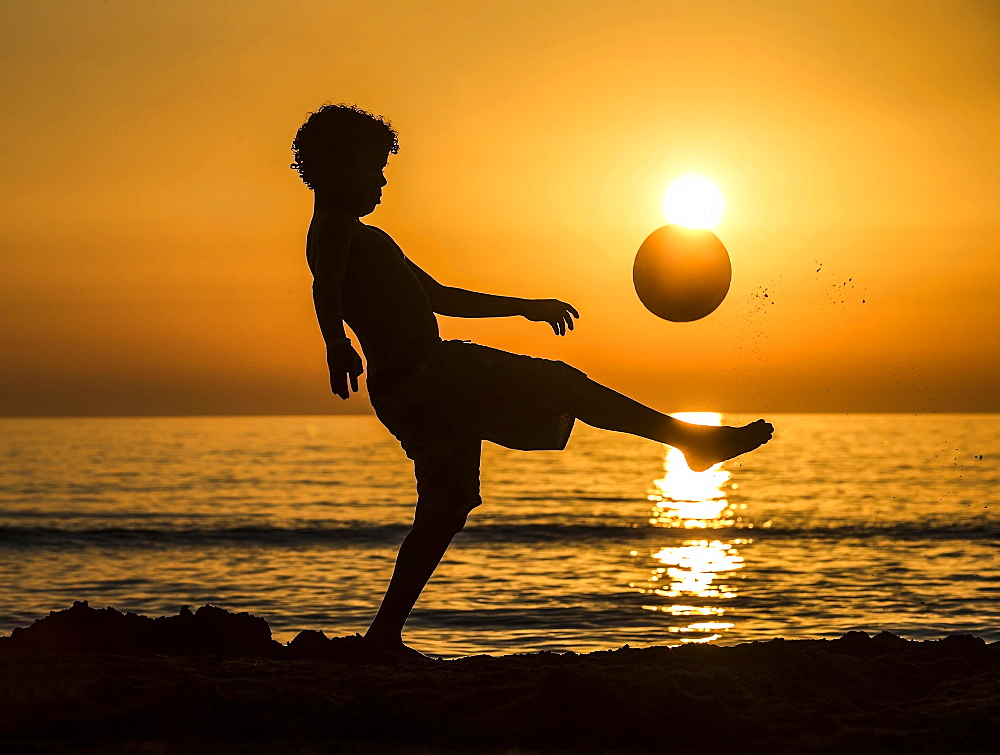 Boy with soccer ball, sunset at the sea, beach, Italy, Europe - 832-381277