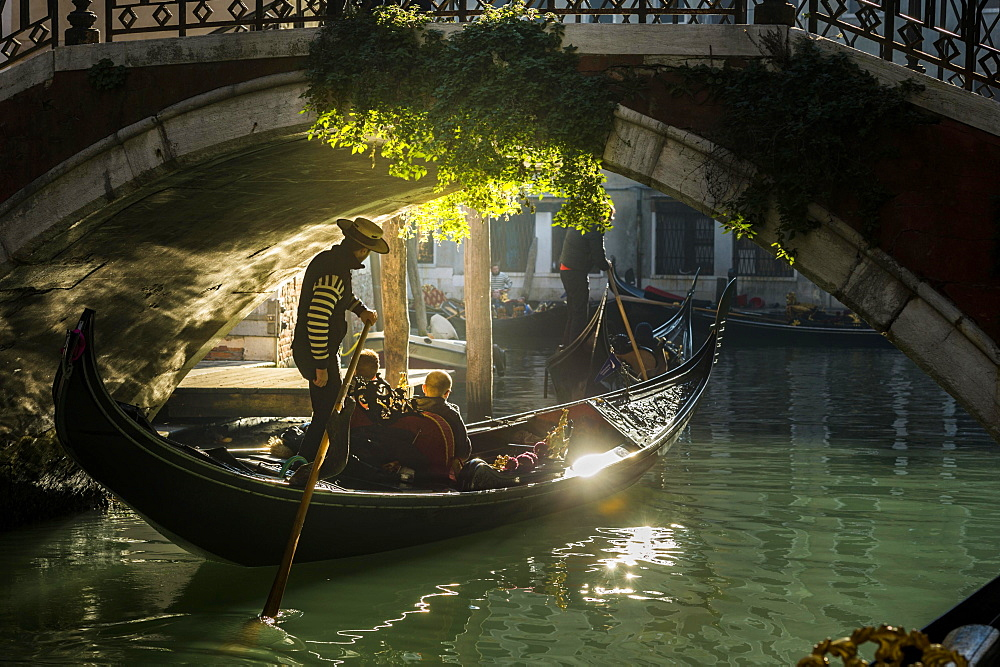 Canal, gondola with gondolier travels under a bridge, Venice, Veneto, Italy, Europe