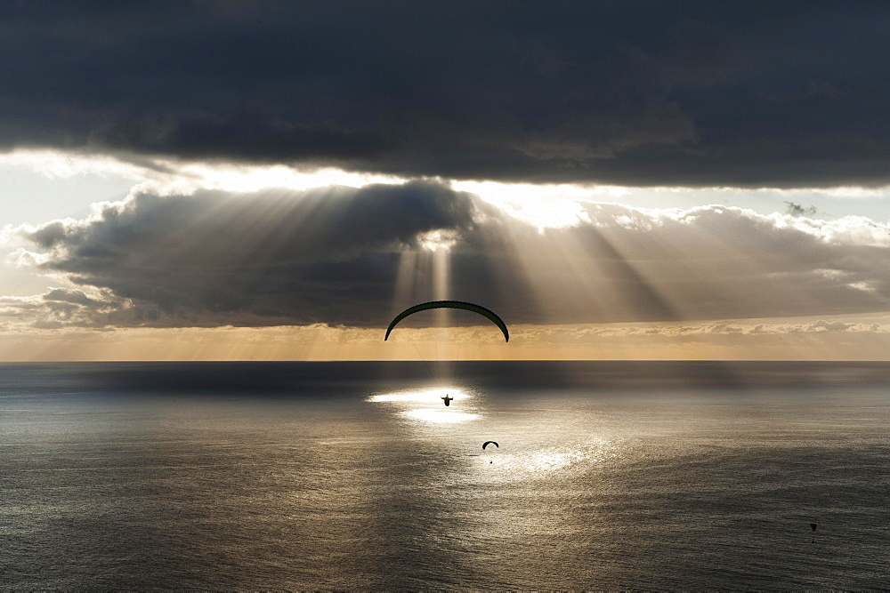 Sun shines behind dark clouds with paraglider over the Atlantic, Puerto Naos, Canary Island of La Palma, Spain, Europe
