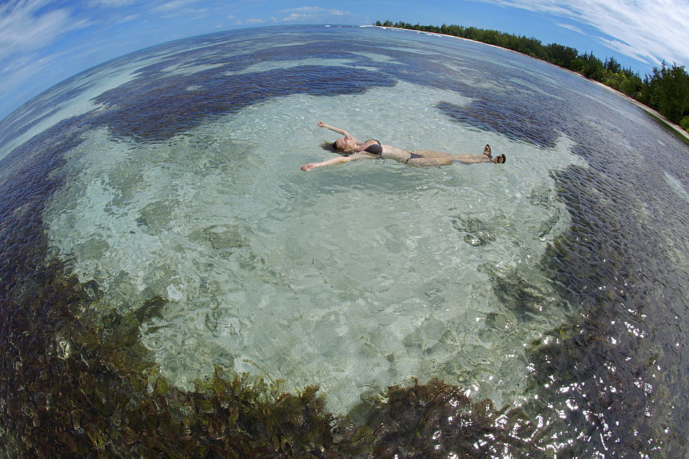 A young woman lying in the water on her back, Denis Island, Seychelles, Africa