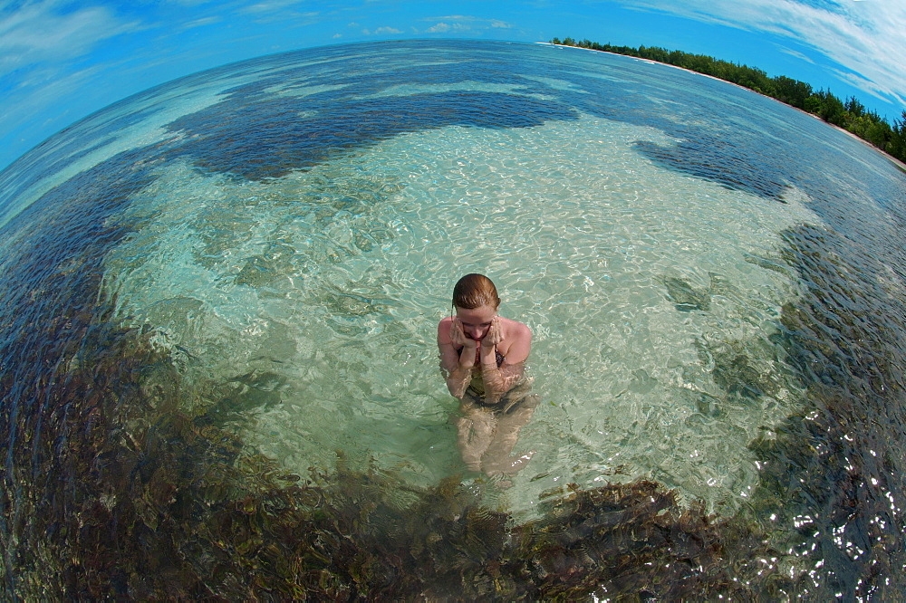 A young woman sitting in water, Denis Island, Seychelles, Africa