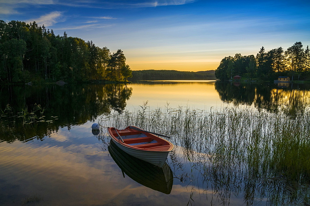 Lake and rowing boat at sunset in Bengtsfors, Dalsland, Sweden, Europe