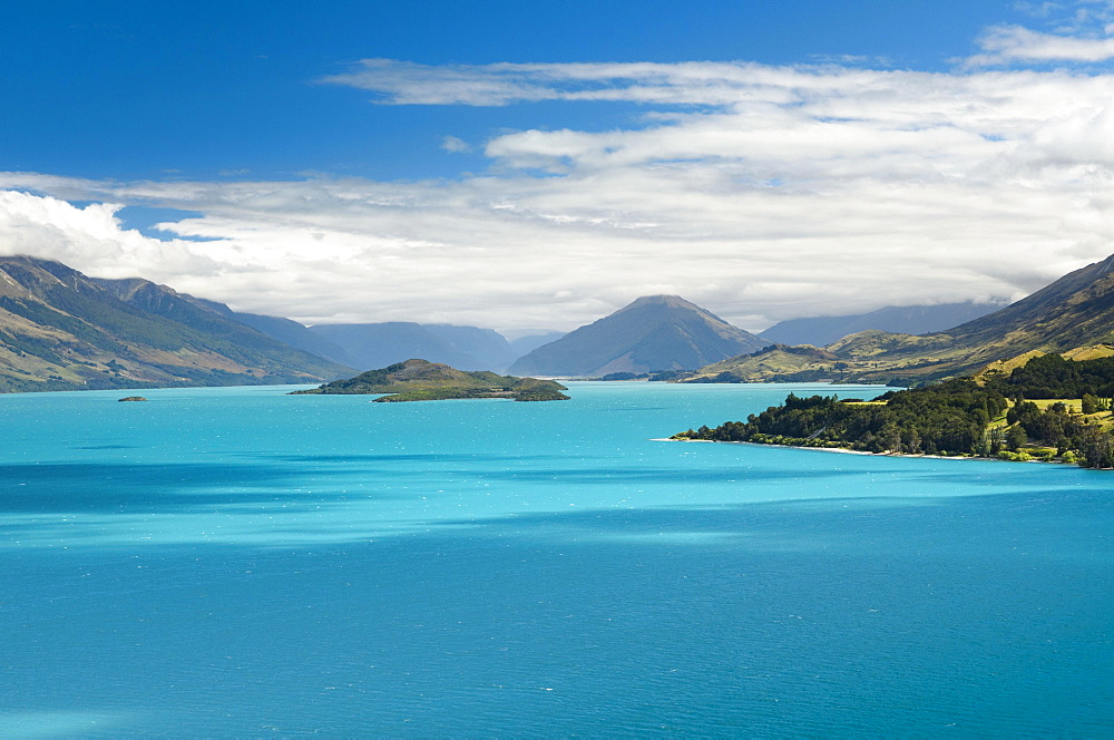 Blue sky with clouds over turquoise lake, Lake Wakatipu, Pig Island behind, near Queenstown, New Zealand, Oceania