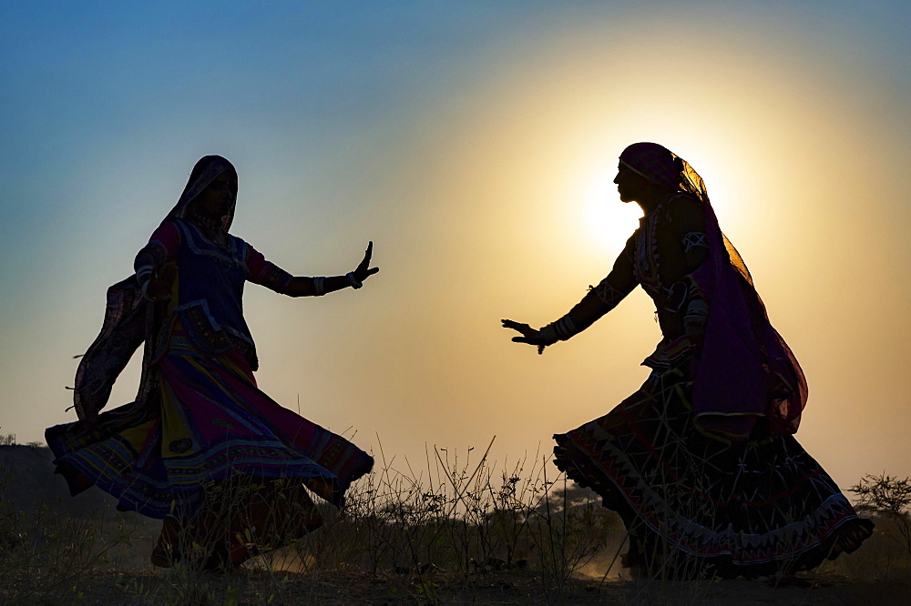 Two young women in dresses dancing in front of the setting sun, Pushkar Camel Fair, Pushkar, Rajasthan, India, Asia