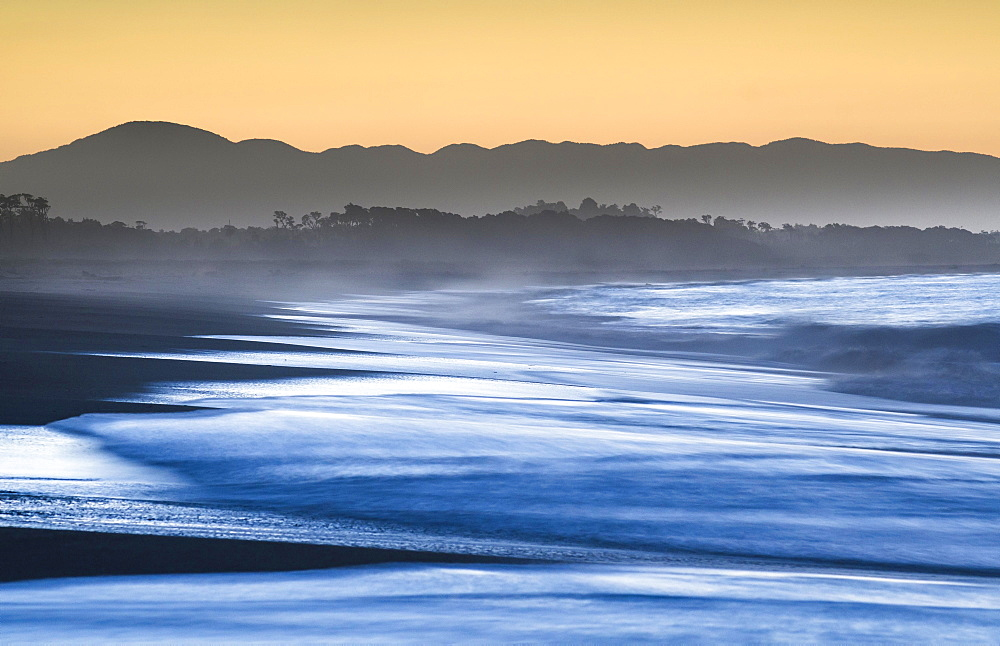 Surf with haze on a wide beach in the evening light, sunset in Haast, West Coast, South Island, New Zealand, Oceania