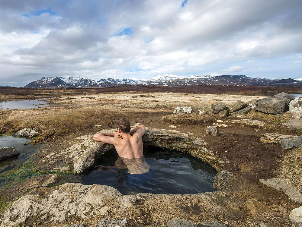 Young man in a hot spring, near Eyjar og Miklaholt, Vesturland, Iceland, Europe - 832-381829