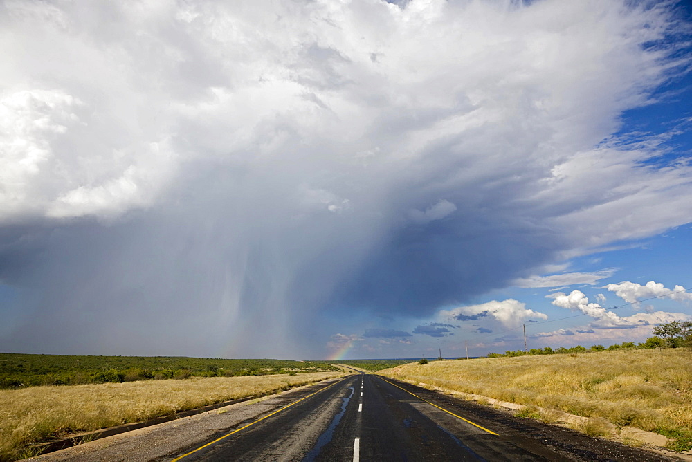 Trans Kalahari Highway, paved road with a rainbow in Namibia, Africa