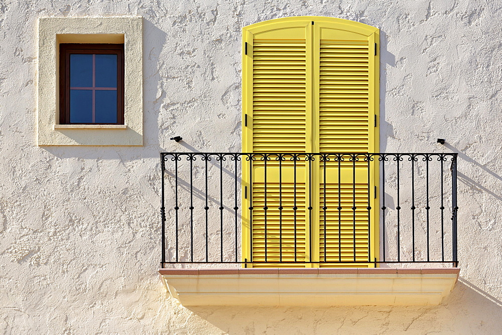 White house facade with a balcony, a yellow balcony door and a small window, Villaricos, Cuevas del Almanzora, Almeria province, Andalucia, Spain, Europe