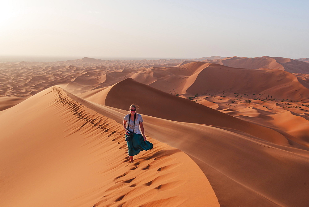 Female hiker on a red sand dune in the desert, dune landscape Erg Chebbi, Merzouga, Sahara, Morocco, Africa