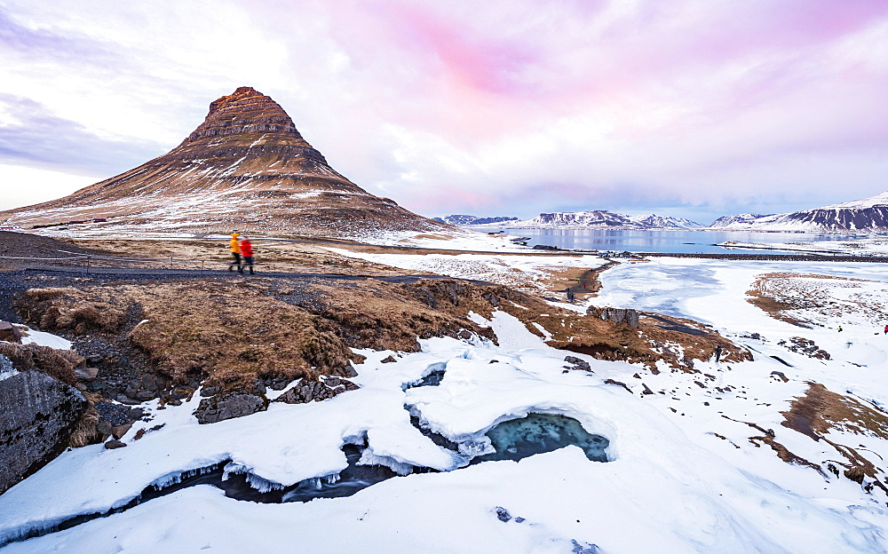 Hikers, Kirkjufell mountain, Kirkjufellfoss waterfall frozen up in front, cloudy sky with sunset, Grundarfjordur fjord, western Iceland, Iceland, Europe